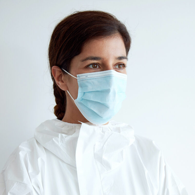 Woman wearing a 3-ply blue surgical face mask